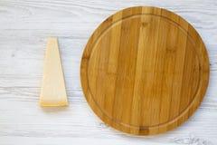 帕尔马干酪和圆的竹委员会片断白色木背景的 顶视图,平的位置,从上面 免版税图库摄影