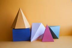 帕拉图式的固体抽象静物画构成 棱镜金字塔长方形立方体在黄色纸背景计算 免版税库存图片