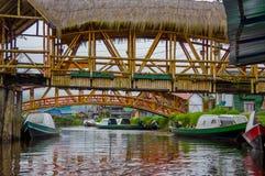 帕斯托,哥伦比亚- 2016年7月3日:一些木头跨接在有些小船的身分在接近la cocha湖的一条河 库存图片