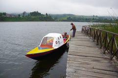 帕斯托,哥伦比亚- 2016年7月3日:停放一条精密小黄色小船的未认出的人在岸旁边在la cocha湖 库存图片