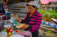 帕斯托,哥伦比亚- 2016年7月3日:加一些焦糖的未认出的妇女到一个薄酥饼在接近la cocha湖的一个地点 图库摄影