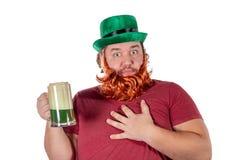 帕特里克斯天党 拿着杯在圣帕特里克的啤酒的滑稽的肥胖人画象  免版税库存图片
