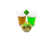 帕特里克` s泡沫似的饮料琥珀色和绿色啤酒的天杯与一棵快餐和三叶草的在白色 免版税库存图片