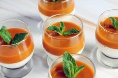 帕纳陶砖点心用与薄荷叶的芒果纯汁浓汤在一张大理石桌上的一块玻璃 库存照片
