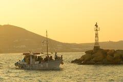 帕罗斯岛,希腊2016年8月5日 享受与一条地方旅游小船的人们巡航在Naoussa地方村庄在帕罗斯岛海岛 免版税图库摄影