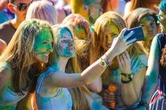 维帖布斯克,白俄罗斯- 2015年7月4日:愉快的女孩采取selfie在Holi颜色节日 库存图片