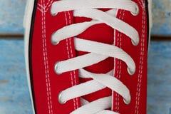系带在一双减速火箭的运动鞋,特写镜头,在蓝色木背景 库存图片