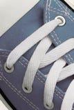 系带在一双减速火箭的运动鞋,特写镜头,在蓝色木背景 库存照片