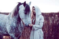 带帽子的外套的女孩有马的,定调子的作用 免版税库存图片