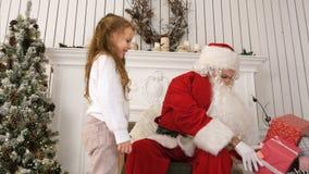 带来圣诞老人的一个礼物和拥抱他的小女孩在他的圣诞节车间 图库摄影