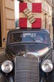 带来在老典雅的奔驰车汽车的圣诞老人礼物 免版税图库摄影