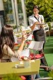 带来妇女咖啡命令餐馆的女服务员 免版税库存图片