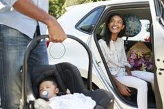带来汽车的父母新出生的婴孩家 免版税库存照片