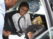带来汽车的父母新出生的婴孩家 库存图片