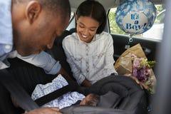 带来汽车的父母新出生的婴孩家 库存照片
