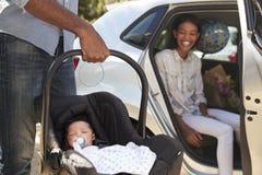 带来汽车的父母新出生的婴孩家 免版税库存图片