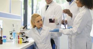 带来液体的小组科学家给女性研究员与显微镜Expertising一起使用它在实验期间 股票录像