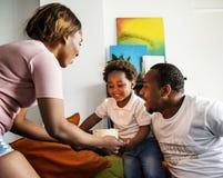 带来生日蛋糕的妈妈给她的孩子 免版税图库摄影