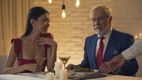 带来票据的侍者给吃老的百万富翁与少女,恋人的晚餐 影视素材