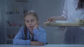 带来膳食的社会工作者给沮丧的女孩在孤儿院坐下雨天 股票录像