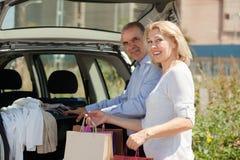 带来袋子的年长夫妇给他的汽车后车箱  图库摄影