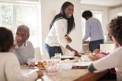 带来食物的黑夫妇给星期天家庭晚餐的桌孩子和祖父母的 免版税库存照片