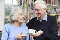 带来妻子茶的老人 免版税库存图片