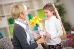 带来黄色花的孙女给她的祖母 免版税库存照片