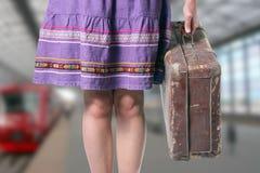 带着一个减速火箭的手提箱的女孩在火车站 免版税图库摄影