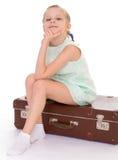 带着一个大和非常老手提箱的小女孩。 免版税库存图片