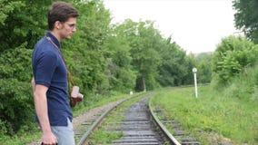 带着一个手提箱的一个年轻人在铁路线 火车在一个大城市丢失,一个年轻人去得到失去在大城市 影视素材