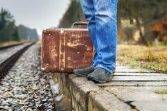 带着一个手提箱的人在铁路的平台 免版税图库摄影