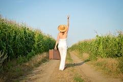 带着一个手提箱的女孩在一条农村路在夏天 免版税库存照片