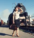 带着一个手提箱的妇女在减速火箭的火车附近的平台 免版税库存图片