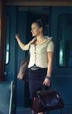 带着一个手提箱的妇女在减速火箭的火车 库存图片