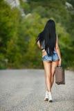 带着一个手提箱的孤独的女孩在乡下公路 图库摄影