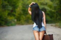 带着一个手提箱的孤独的女孩在乡下公路 免版税库存照片