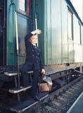 带着一个手提箱的小男孩在减速火箭的火车 免版税库存照片
