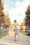 带着一个手提箱的美丽的女孩在公园 免版税图库摄影