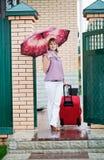 带着一个红色手提箱的愉快的女孩 图库摄影