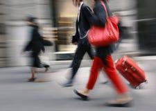 带着一个红色袋子和手提箱的人步行沿着向下街道的 免版税库存图片