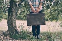 带着一个老棕色手提箱的年轻人在一处自然风景 库存图片