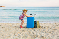 带着一个蓝色手提箱的美丽的小姐在海滩 人、旅行、假期和夏天概念 免版税库存图片