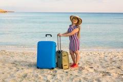带着一个蓝色手提箱的美丽的小姐在海滩 人、旅行、假期和夏天概念 库存图片