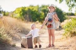 带着一个更老的姐妹和一个大手提箱的弟弟 免版税库存图片