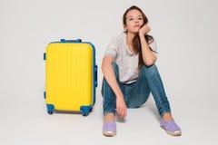 带着一个黄色手提箱的女孩 免版税库存图片