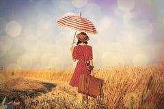 带着伞和手提箱的少妇 免版税库存图片