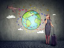 带着准备好的手提箱的少妇乘飞机旅行环球 免版税库存照片