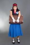 带着减速火箭的手提箱的哀伤的妇女 免版税库存照片