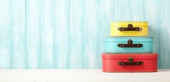 带着减速火箭的样式手提箱的旅行概念在蓝色木backgro 免版税图库摄影